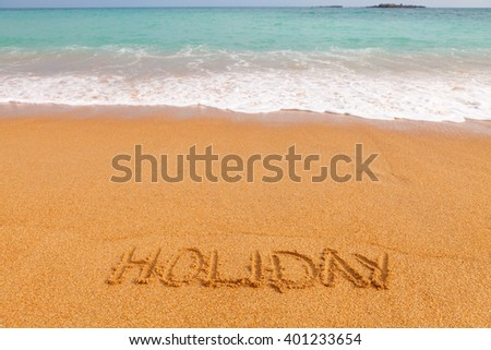 """Inscription """"HOLIDAY"""" made on beautiful beach by the blue sea - stock photo"""