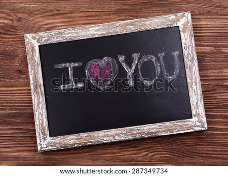 Inscription I LOVE YOU on blackboard on wooden background - stock photo