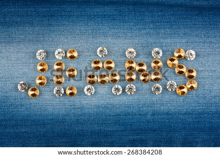 Inscription jeans made of rhinestones on jeans background - stock photo