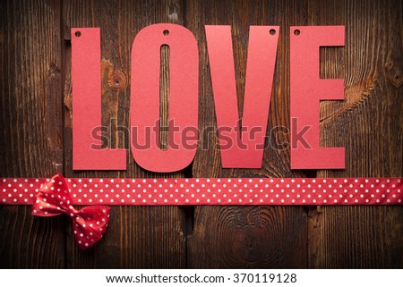 Inscription love and a red ribbon on wooden background - stock photo