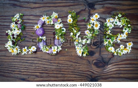 Inscription LOVE made of flowers and leaves on vintage wooden table background. Word love made of flowers.Top view.