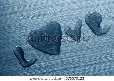 Inscription Love with heart on a metal surface