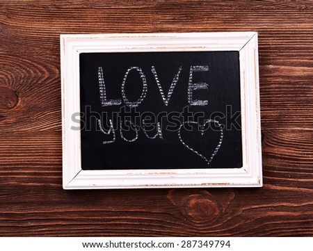 Inscription LOVE YOU on blackboard on wooden background - stock photo