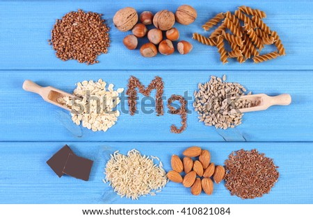 Inscription Mg, ingredients and products containing magnesium and dietary fiber, healthy nutrition, wholemeal pasta, sunflower, buckwheat, oatmeal, brown rice, linseed, hazelnut, almonds, chocolate - stock photo
