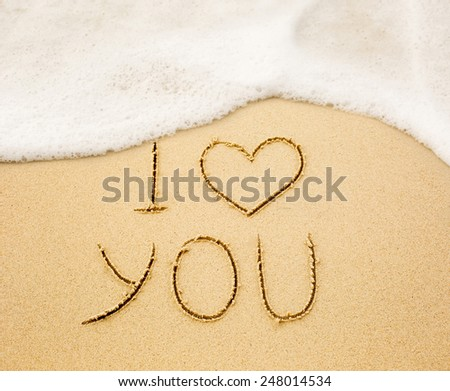 Inscription of I love you written on wet yellow beach sand being washed out with the sea. Concept of celebrating the St. Valentine's day at some exotic place - stock photo