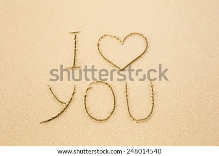 Inscription of I love you written on wet yellow beach sand. Concept of celebrating the St. Valentine's day at some exotic place - stock photo