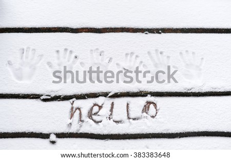 Inscription on snow - Hello. Hand palm prints also - on snow. - stock photo