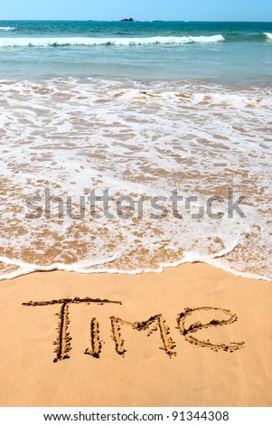 inscription time on wet golden beach sand in front of the ocean. - stock photo