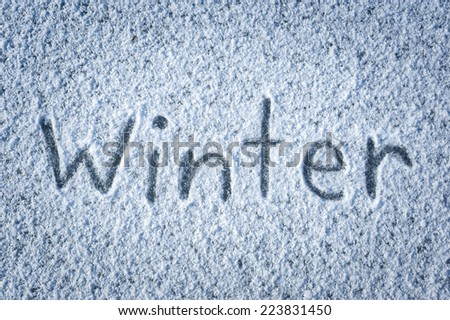 inscription winter on snow-covered ice - stock photo
