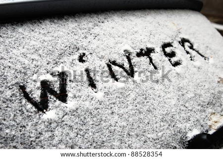 inscription winter on snow on the back window of car - stock photo