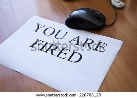 "Inscription ""You are fired"" on the sheet of white paper - stock photo"