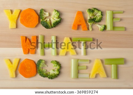 inscription you are what you eat on wooden background, text from farm products, letters from vegetables, carrots, celery, potatoes, broccoli, closeup, chopped vegetables, macro - stock photo