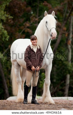 inseparable - young girl and gray big shire in wood. - stock photo