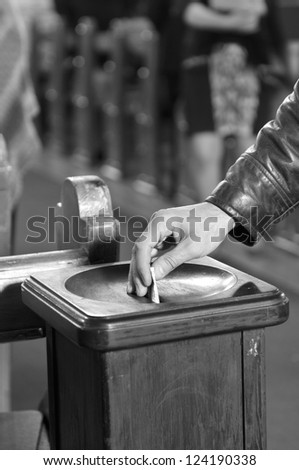 Inserting a banknote into offertory box - stock photo