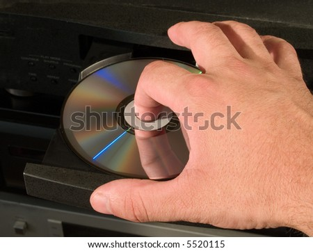 inserting blu-ray dvd disk in player - stock photo