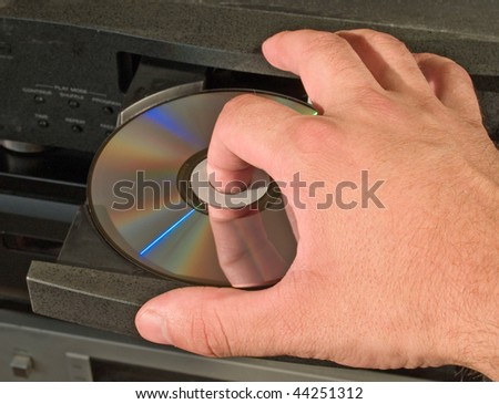 inserting dvd disk in player - stock photo