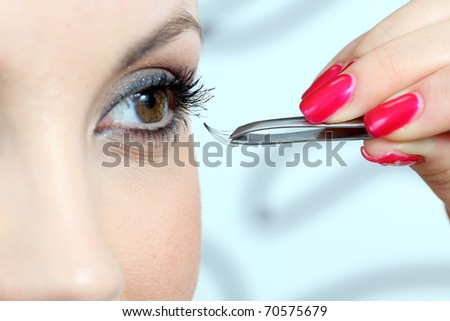 Insertion of false eyelashes. Close up.