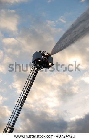 Inservice training on a new 100 foot platform fire truck.  Working with ladder placement and elevated master streams. - stock photo