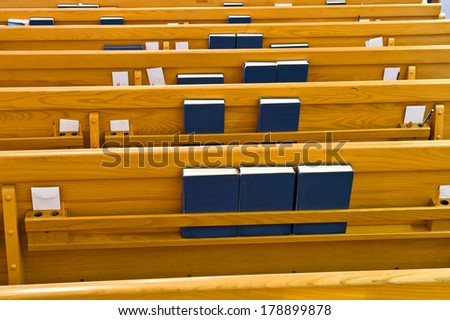 Inside a church looking at the back of the pews - stock photo
