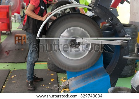 Inside a garage - changing wheels-tire during spinning wheel