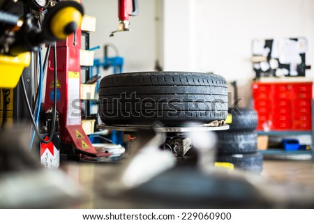 Inside a garage - changing wheels/tires (shallow DOF; color toned image) - stock photo