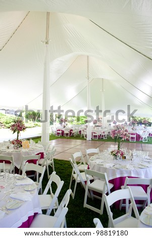 Inside a large wedding tent set up for an outdoor reception - stock photo