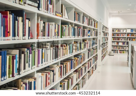 Inside a library with white book shelves and white wall