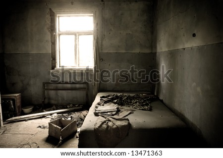 Inside abandoned house. View on messy bed and window. Grunge scene.