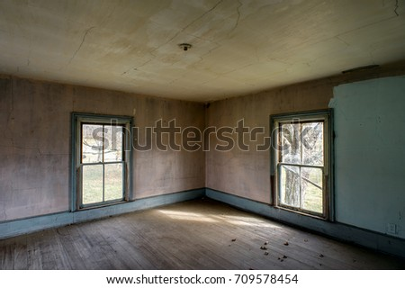 Inside an abandoned farm house in southern Kentucky with vintage four-pane windows, hardwood floors and brown and teal wallpaper.