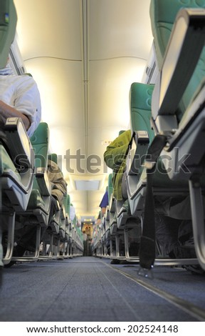 inside an airplane with at background a stewardess in the pantry - stock photo
