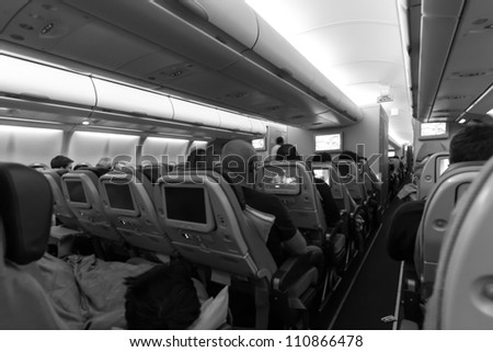 Inside an airplane with passengers - stock photo