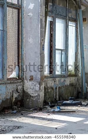 Inside An Old Abandoned Industrial Building, Factory. Many Different Garbage. Broken Glass On The Windows, Damaged Walls. Heavy Contamination. - stock photo