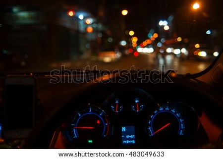 Inside car with bokeh lights from traffic jam on night time for background.