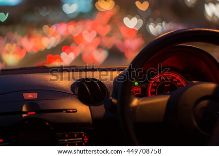 Inside car with heart bokeh lights from traffic jam on night time for background.