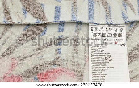 "Inside jersey fabric background with washing label with inscription ""Designed with passion &  love in Germany"" and ""Made in India""  in several languages according multilingual label EU law. Text Place - stock photo"