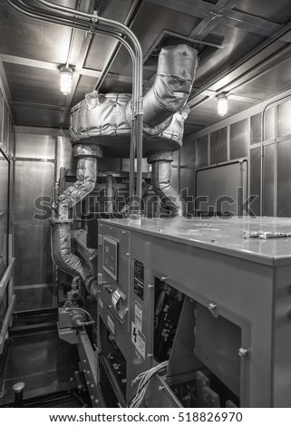 Inside of diesel generator weatherproof enclosure, monochrome image.  Sound attenuated reducing decibel level.