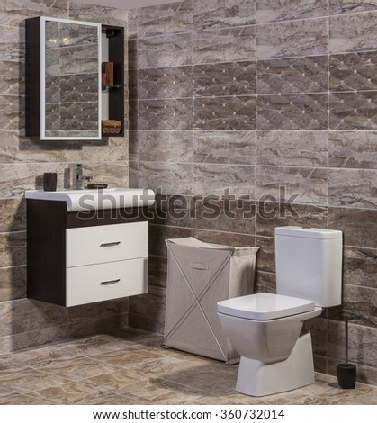 Inside of fashionable bathroom - toilet and sink and modern ceramic tiles - stock photo