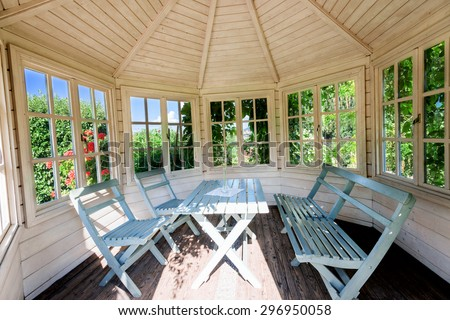 Inside of outdoor wooden gazebo at sunset on summer