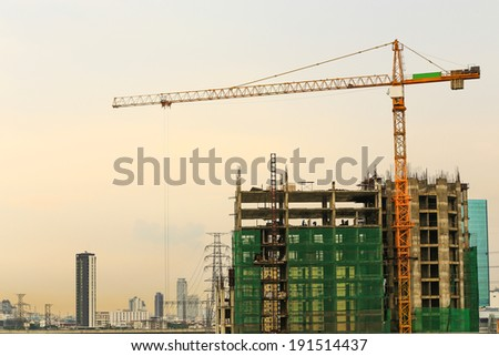 Inside place for  tall buildings under construction and cranes under a blue sky.