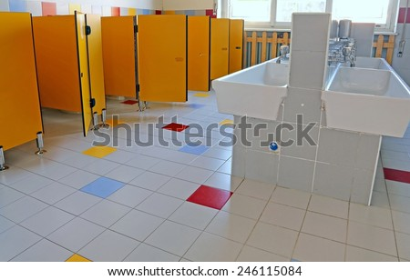 inside the bathroom of the nursery school with white ceramic sinks and doors yellow - stock photo