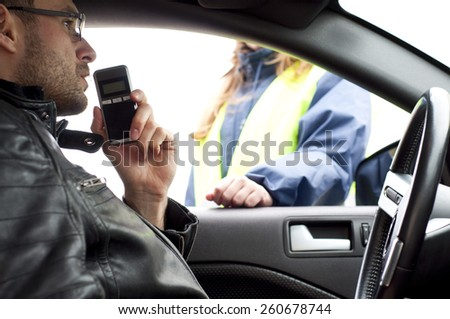 Inside the car view of a young drink and drive crashed driver due to being subject to test for alcohol content with use of breathalyzer - stock photo