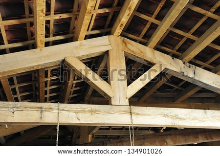 inside the roof structure with wooden beams traditional style