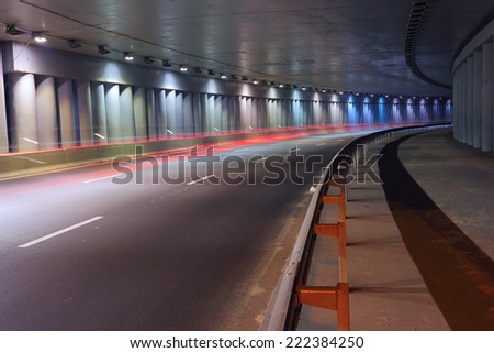 Inside the urban tunnel where the highway is illuminated with car lights traces - stock photo