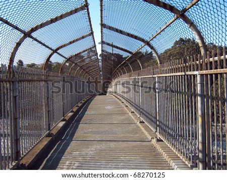 inside view of a covered metal fence pedestrian overpass in San Francisco - stock photo