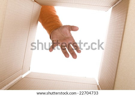 inside view of cardboard box with a hand trying to reach the content (selective focus) - stock photo