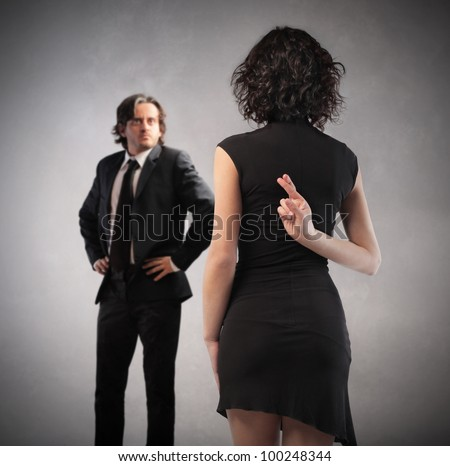 Insincere woman crossing her fingers behind her back with husband in front of her - stock photo