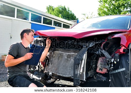 Inspecting car damage after crash. - stock photo