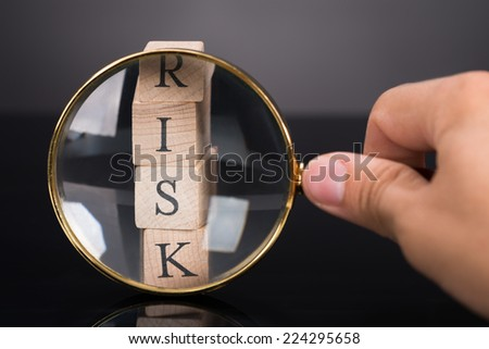 Inspecting risk blocks with loupe over black background - stock photo