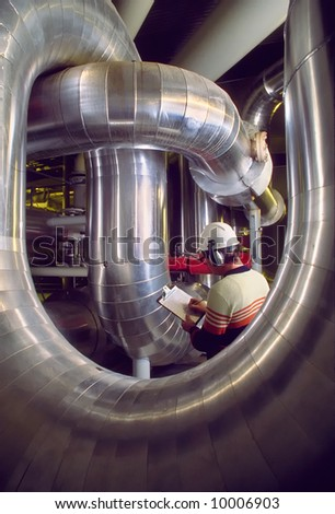 Inspector in an industrial plant - refinery, pipes, and air ducts