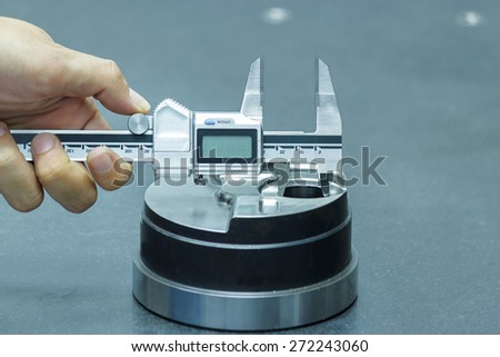 Inspector Measuring parts by Vernier Caliper - stock photo